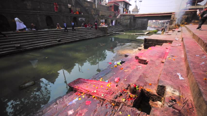 KATHMANDU, NEPAL - APRIL 11, 2016: Ritual place with lingams where ceremony of body washing in Bagmati river before cremation take place. Pashupatinath Temple, one of the sacred temples of Hindu faith
