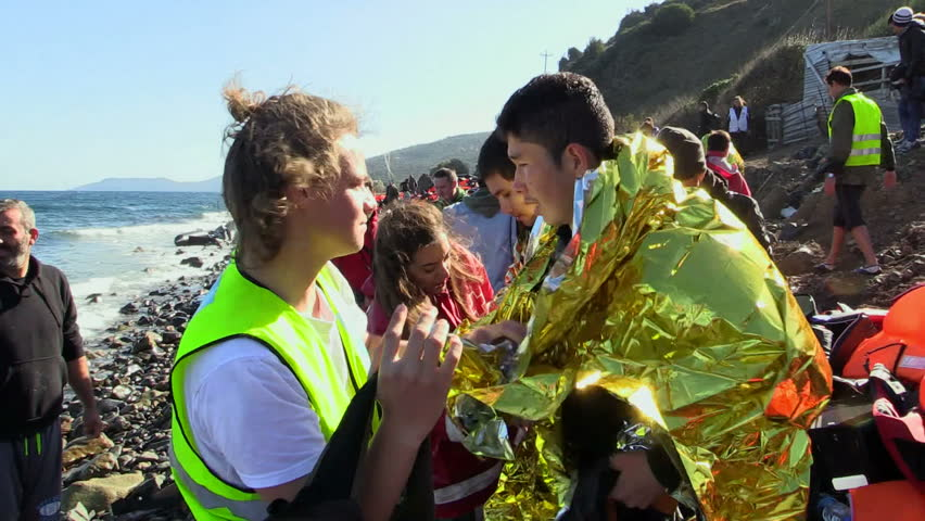 LESVOS, GREECE - NOV 2, 2015: Volunteers provide first aid to the refugees on the shore.