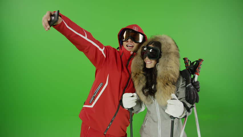 Beautiful couple taking selfie with ski suits on green screen and demonstrating different versions of emotions and poses.  With photo camera flash light. Shot on RED EPIC DRAGON Cinema Camera. #21086503