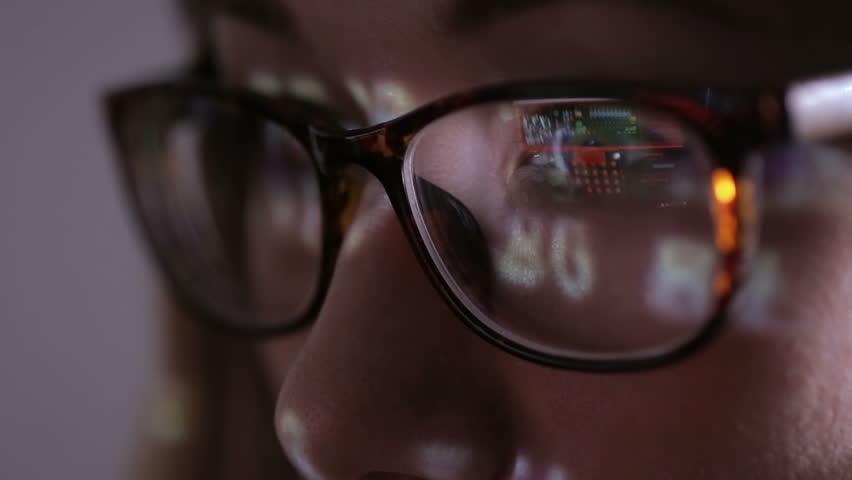 Computer screen reflected in hacker's glasses. Female hacker in dark working with data code.