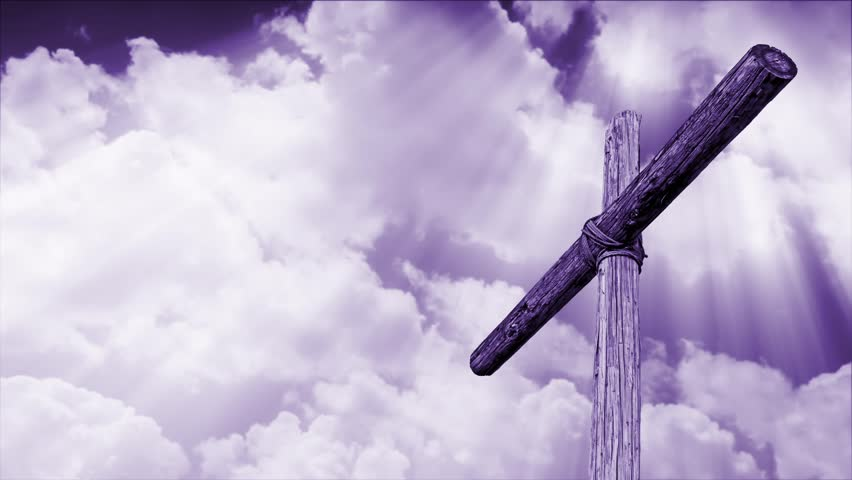 wooden cross backed by time lapse motion clouds with shining, penetrating shafts of light - violet tone