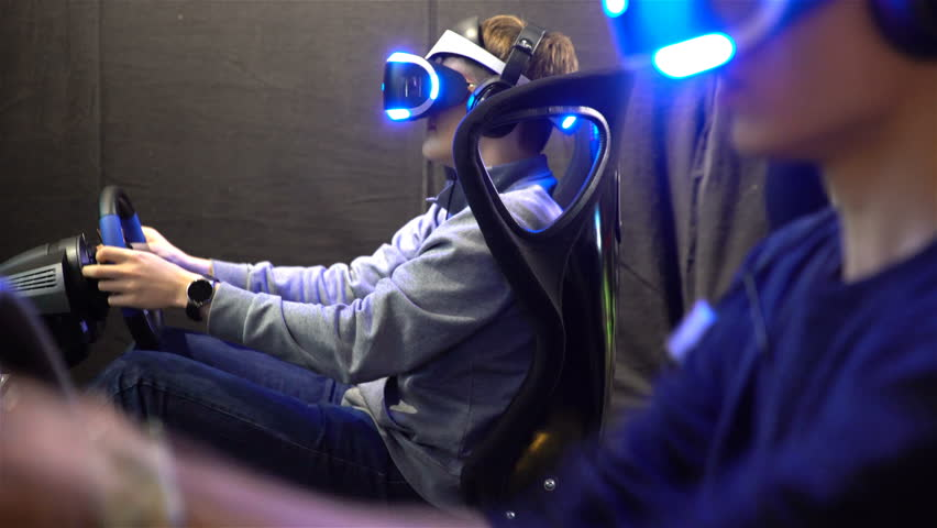 HELSINKI, FINLAND - NOVEMBER 4, 2016: VR games. Teens use virtual reality helmets, racing simulator. The newest gadgets on GAME EXPO in the exhibition center Messukeskus.