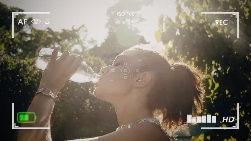 Seen through a camera viewfinder. A pretty girl drinking water from a plastic bottle, right in front of the sun. Profile shot, outdoors, public park.