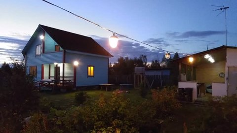 MOSCOW - AUG, 4, 2015: Two-storey country house and small summer house with woman on yard in twilight, mobile phone video. Many people have vacation homes and only come to Moscow from time to time.