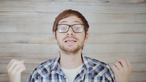 Young man in glasses talking to camera