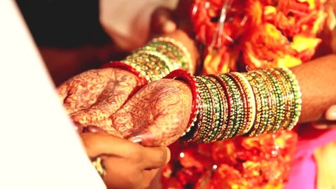 Indian wedding ritual / Bride and groom joining hands during an Indian wedding ritual