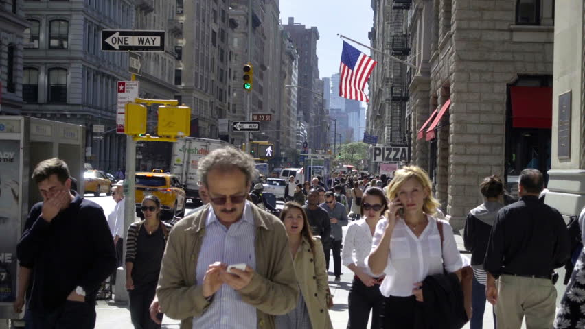 NEW YORK - SEPTEMBER 25, 2016: People Walking, Man Checking Cell Phone, Crowded Busy Midtown 5th Ave Manhattan Street with American flag in summer, NYC. Fifth Avenue is a popular street in the city.