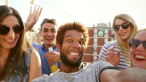 Close up of smiling guy filming himself and cheerful friends at rooftop party on sunny day, graded