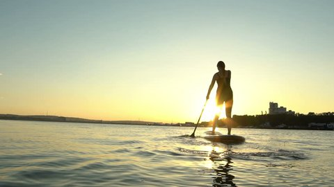 Silkhouette of young woman on Stand Up Paddle Board. Sunset in a city on background. Slow motion.