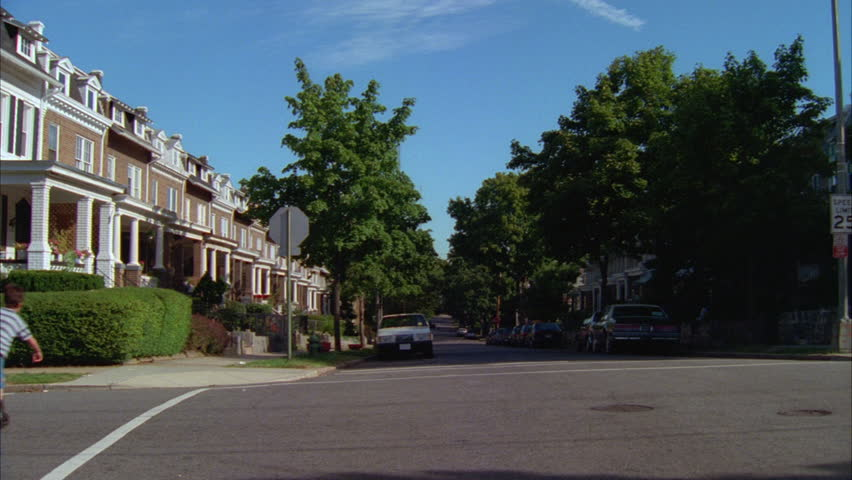 Day Pan left up Raked left two story red brick attached row houses white trim steps up porches Boy skates thru | Shutterstock HD Video #21207643