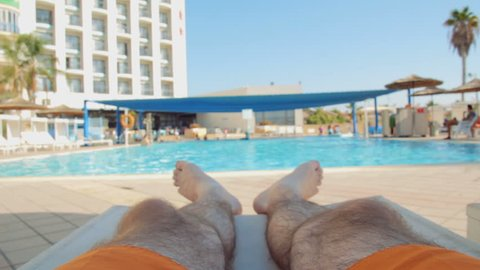 Man relaxing and sunbathing on sunbed by pool. Pov on the swimming pool in a resort.