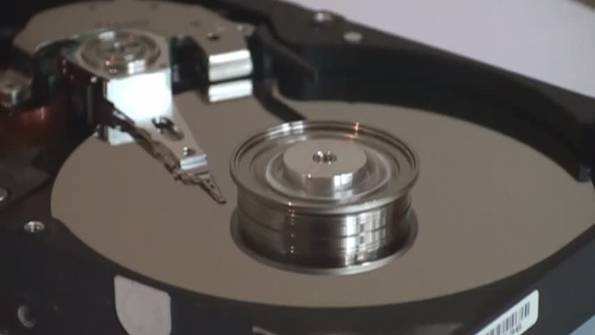 Metal circle plate and magnetic head inside hard disk drive reading and writing data   Shutterstock HD Video #21255601