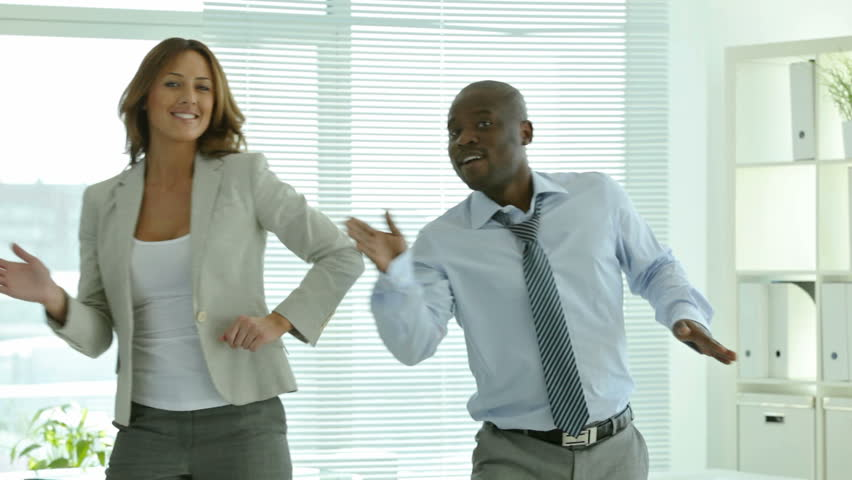 Businesspeople dancing cheerfully in office in front of the camera