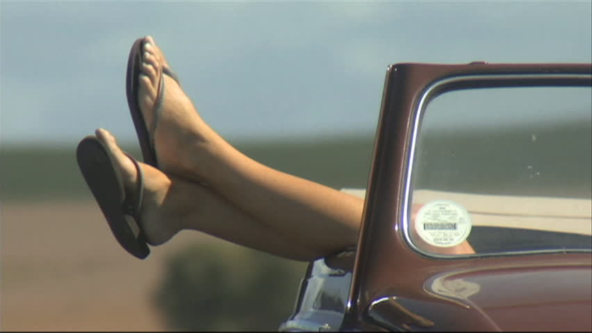 CLOSE UP PAN OF A YOUNG WOMAN LYING IN A CAR