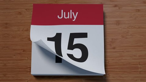 Calendar for July on wooden table flipping through days of month
