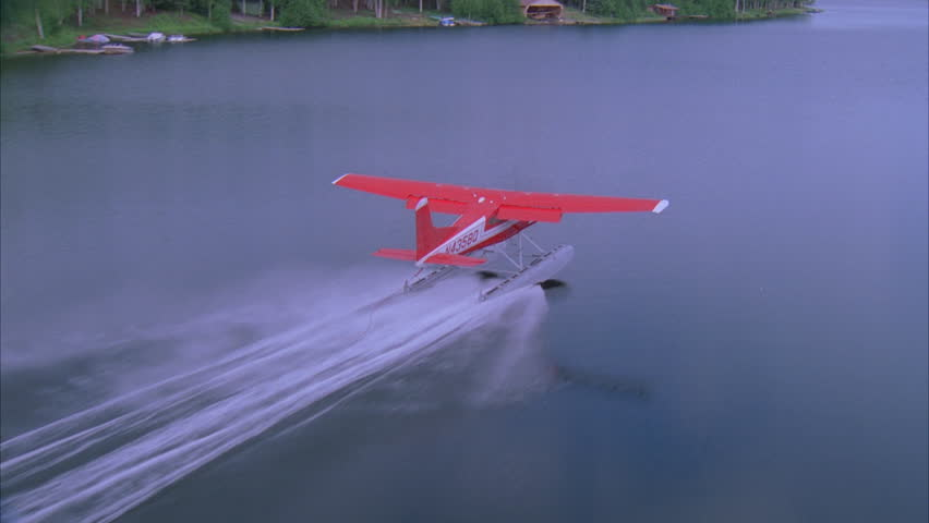 day Aerial various angles seaplane, over dense lush green woods forest, glassy lake, secluded homes, rural roads Seaplane touches down lake, keeps momentum, takes again Banks left