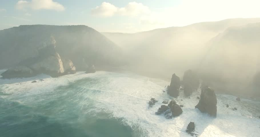 Beautiful aerial or drone shot along the coast of Portugal on a sunny day. Epic cliffs and ocean waves birds eye view during sunrise. Untouched, powerful nature. Cabo da Roca, Portugal Europe. | Shutterstock HD Video #21359914