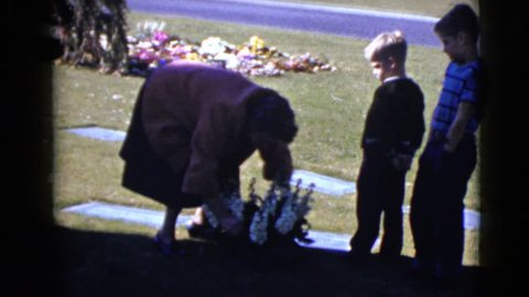 CLARKSDALE, ARIZONA 1968: two boys quietly watch as a woman straightens up a bouquet of flowers by a tombstone in a cemetery.