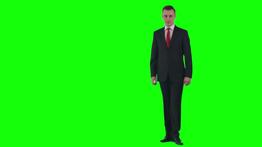 Businessman in suit walking before green chroma key background talking and gesticulating  | Shutterstock HD Video #21385153