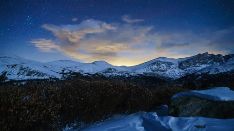 Clouds and Stars timelapse with snow capped mountains + far away city lights