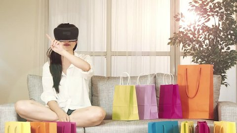 asian woman experience shopping online with VR headset sitting on sofa colorful shopping bags around. indoor living room background