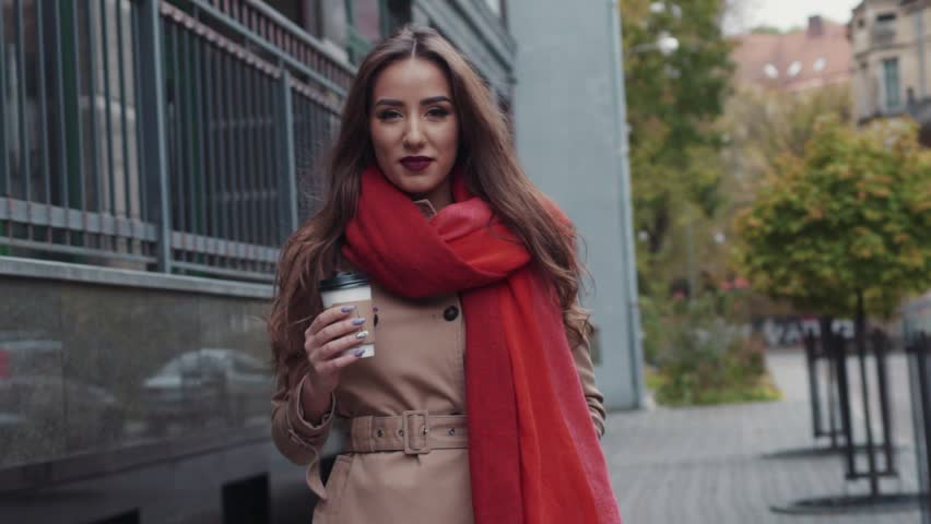 Beautiful young girl with an attractive appearance, adorable look, curly hairstyle, scarf and autumn coat in the city. Amazing view of business lady with a cup of coffee walking down the city street.
