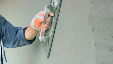 Man's hand plastering a wall with trowel. Construction worker at work. Construction worker smoothing out wall with trowel.