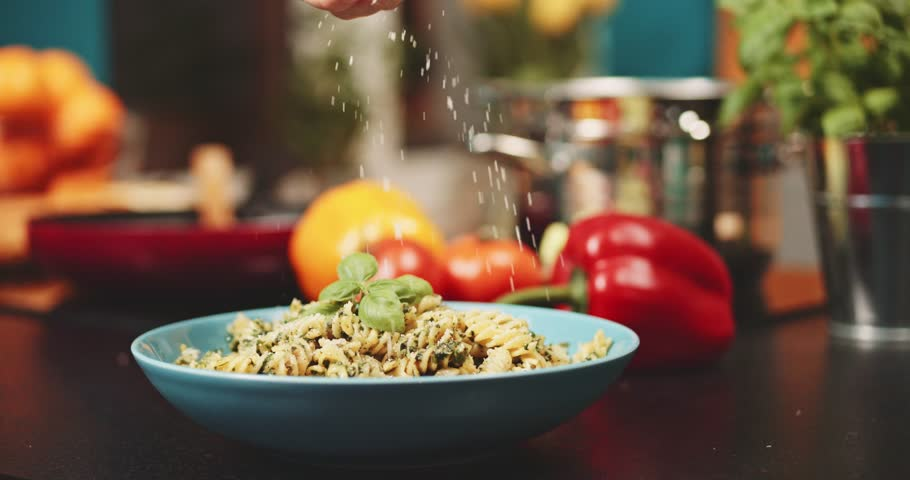 Putting parmesan cheese on pasta slow motion dolly shot woman hands covering fusilli pasta with italian cheese at the kitchen background delicious food home cooking healthy eating   Shutterstock HD Video #21469375
