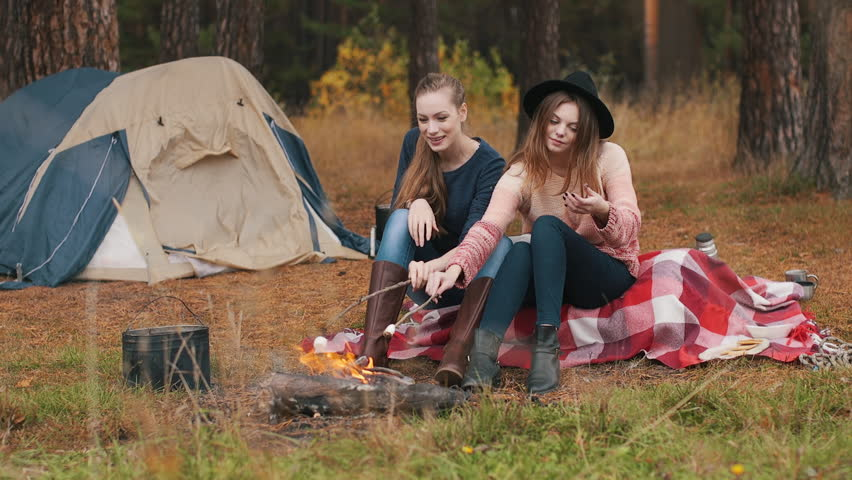 Two girlscook marshmallow at campfire. They smile and have fun Autumn forest.