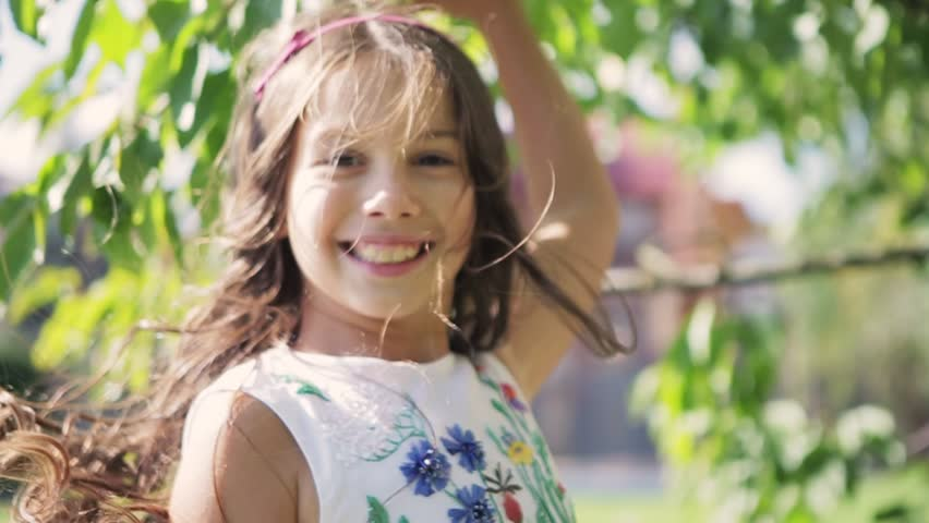 Close up view of little brunette girls curls in a motion, she is in a white dress, jumps, runs, cross the garden by the house, touches tree leaves, turns to camera and gives an adorable smile.
