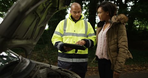 4k, Roadside rescue mechanic and a young woman review work on a digital touchcreen tablet.