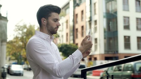 Man wearing earphones and having a videocall on smartphone