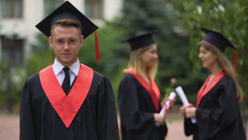 Graduation ceremony, happy man in academic dress looking into camera, laughing | Shutterstock HD Video #21534253