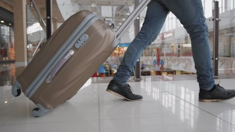 Young man pulling suitcase in modern airport terminal. Travelling guy wearing smart casual style clothes walking away with his luggage while waiting for transport. Rear view. Close-up