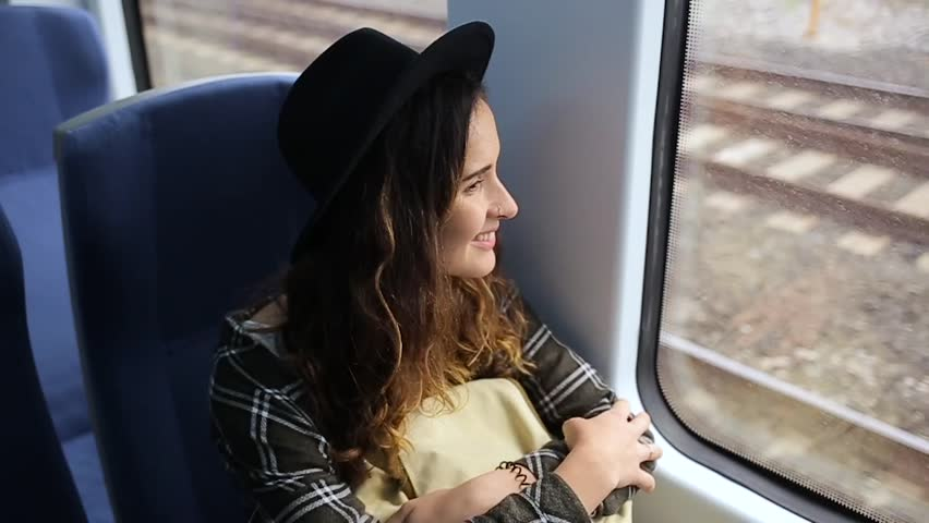 Girl is smiling girl with a backpack on a train.