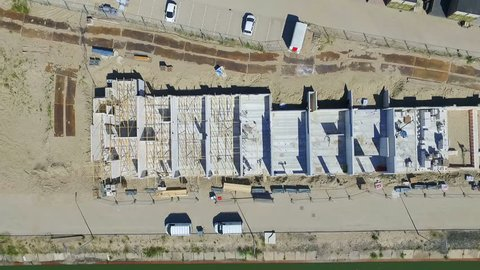 FULLHD Aerial View of a construction site with houses and walls on the ground floor showing working man. Sunny weather. Drone shot, 90 degrees angle, descending movement.