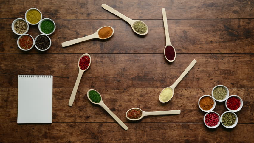 Spices in spoons and bowls moving on wooden background. Stop motion animation.