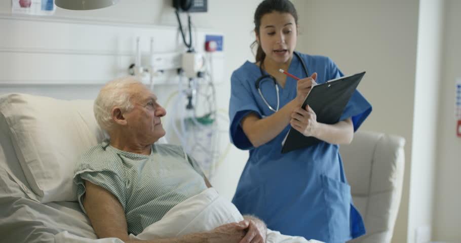 4K Caring medical worker in hospital talking to elderly man at his bedside (UK-Oct 2016) #21577363