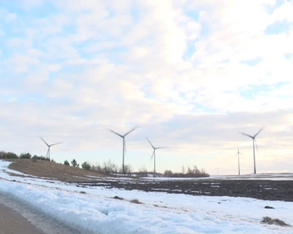 speed up view windmills rotating and clouds flow in sky. melting snow fields.