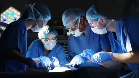 4K Team of surgeons in operating theater performing operation on a patient. (UK-Oct 2016)