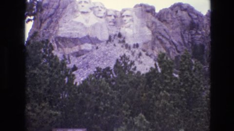 SOUTH DAKOTA 1974: man viewing and photographing mount rushmore, surrounding hills on partly cloudy day