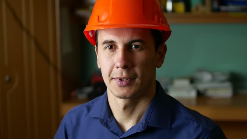 man construction worker in a hard hat portrait indoor - 4K stock video clip