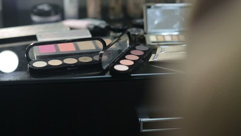 Open MakeUp palette lying on the table in front of a mirror stylist. Multi-colored shade in the trendy set. The colors of the rainbow in a beauty salon. Fashion show. Backstage.