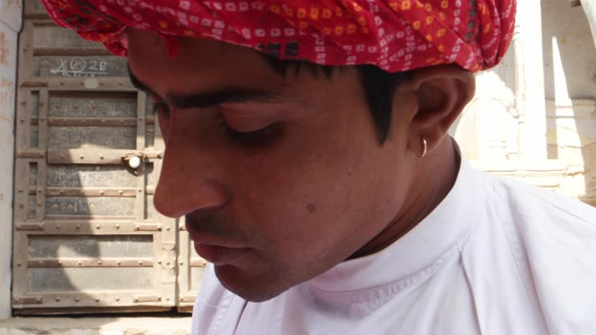 Close up of a handsome Indian man in traditional clothing talking on the phone cell happy