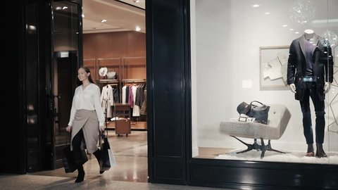 Woman coming out of the clothes store with bags. Girl go from entrance of luxury shop in mall.