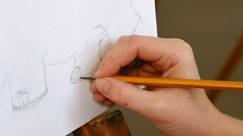 Female artist draws a pencil sketch drawing on canvas easel in art studio student girl