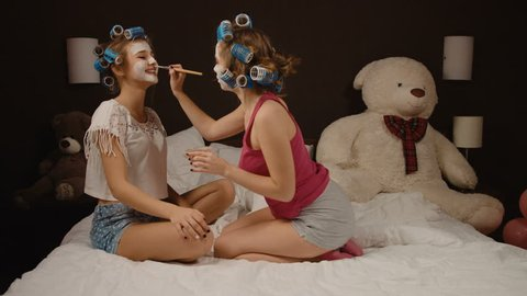 Two cute smiling friends with curlers on hair making masques on the bedroom.