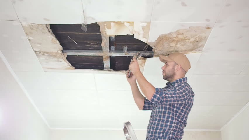 young man makes an emergency inspection of ceiling and use Tablet PC. public utilities. Ceiling panels damaged huge hole in roof from rainwater leakage.Water damaged ceiling , Insurance agent.