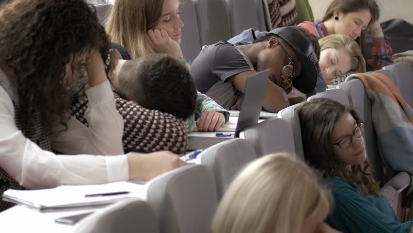A lot of tired young people sleeping in the lecture hall during a boring presentation. Unmotivated young students feeling exhausted in the auditorium during a presentation. | Shutterstock HD Video #21688660