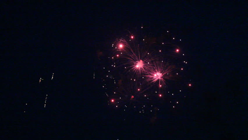 Multiple bursts of fireworks during a night time celebration for the Fourth of July